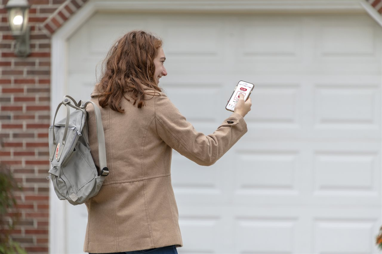 a woman looking at her phone outside the garage | GC Home Inspection | Connectivity Chicago