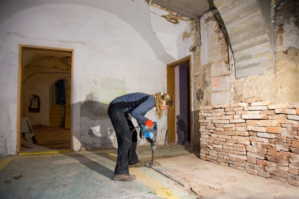 woman drilling the basement floor | GC Home Inspection  | Bathroom in the basement Pearland
